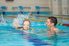 O instrutor ensina a natação da menina em uma associação fotos de stock