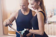 O instrutor escreve um programa fitness que treina a menina fotografia de stock