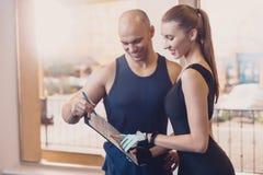 O instrutor escreve um programa fitness que treina a menina imagem de stock