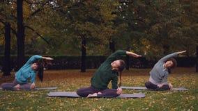 O instrutor fêmea da ioga está mostrando esticando os exercícios que relaxam então na posição de lótus com os olhos fechados que  filme
