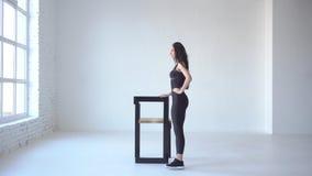 O instrutor fêmea magro desportivo está fazendo pontapés quando se inclinar na cadeira no branco isolou o estúdio Vista completo  vídeos de arquivo