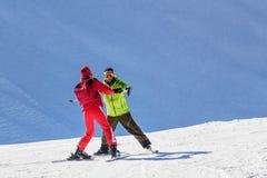 O instrutor masculino ensina o esqui a uma jovem mulher em um dia ensolarado no fundo nevado da inclinação Foto de Stock