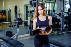 O instrutor pessoal da jovem mulher escreve o plano de treinamento em um caderno fotos de stock