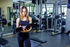 O instrutor pessoal da jovem mulher escreve o plano de treinamento em um caderno fotografia de stock