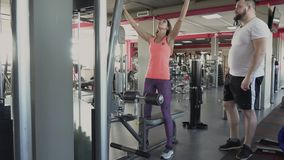 O instrutor pessoal mostra a homem como fazer o exercício no simulador no gym O indivíduo está indo balançar seus músculos do pé  video estoque