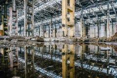 O interior, o celling e as colunas industriais abandonados do salão refletem em águas imóveis Imagens de Stock
