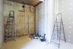 O interior da sala durante de instala da placa de gesso para fazer paredes da gipsita na parede de tijolo em um apartamento está  imagem de stock