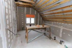 O interior do apartamento da sala com nova janela e materiais casa-fez o andaime, brocas, nível durante na renovação fotografia de stock royalty free