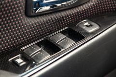O interior do carro com uma vista do painel, das janelas e dos botões do espelho com guarnição cinzenta e vermelha da luz - fotografia de stock royalty free
