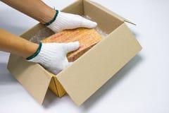 O invólucro com bolhas de ar da posse do homem da mão, para a embalagem e o produto da proteção rachou-se imagens de stock