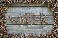O inverno da inscrição com as varas de madeira no fundo de madeira Fotografia de Stock