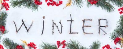 O inverno da palavra escrito com as varas de madeira quebradas no backgr da neve Foto de Stock