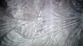 O inverno deixa o teste padrão do gelo na janela Imagens de Stock