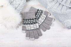 O inverno fez malha luvas, chapéu forrado a pele e pulôver no fundo de madeira branco Grupo de roupa feita malha cinza Imagens de Stock