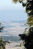 O inverno nas montanhas encontra a mola no vale Fotos de Stock Royalty Free