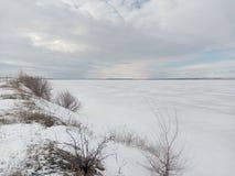 O inverno, neve, nublado, rio sob o gelo, pesca do gelo, céu nubla-se, o horizonte branco, estepe branco imagem de stock