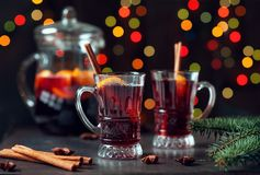 O inverno tradicional ferventou com especiarias o vinho no vidro do vintage e no ornamento do Natal no fundo das luzes, foco sele Fotos de Stock Royalty Free