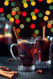 O inverno tradicional ferventou com especiarias o vinho no vidro do vintage e no ornamento do Natal no fundo das luzes, foco sele Fotografia de Stock