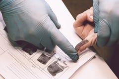 O investigador toma impressões digitais do suspeito no crime A investigação é um crime crime fotografia de stock