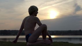O iogue feliz senta-se em uma posição da águia sobre um banco do lago no slo-mo vídeos de arquivo