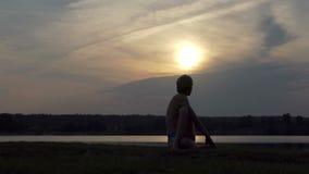 O iogue novo senta-se em um asana da águia em um banco do lago no slo-mo filme