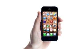 O iPhone 5 de Apple realizou na mão no branco Fotos de Stock Royalty Free
