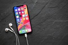 O iPhone o mais atrasado X da geração com fones de ouvido Imagens de Stock