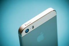 O iPhone 5s de Apple do ouro no fundo do papel azul Fotografia de Stock Royalty Free