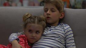 O irmão cansado e a irmã que olham a tevê na noite, menino protegem a menina assustado, horror filme