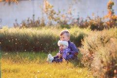 O irmão com a irmã mais nova senta-se em um gramado Fotos de Stock Royalty Free