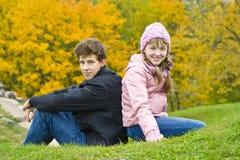 O irmão com irmã senta-se de encontro às folhas amarelas Imagem de Stock