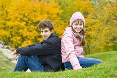 O irmão com irmã senta-se de encontro às folhas amarelas Imagens de Stock Royalty Free