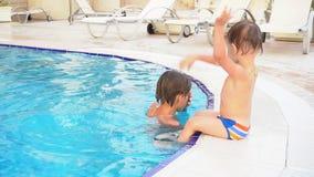 O irmão de dois meninos banha-se na piscina no recurso video estoque