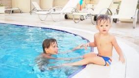 O irmão de dois meninos banha-se na piscina no recurso vídeos de arquivo