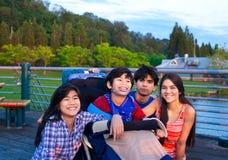 O irmão e as irmãs fora, pendurando para fora no parque com desabilitaram Fotografia de Stock Royalty Free