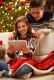 O irmão e a irmã apreciam na Noite de Natal com música da tabuleta foto de stock royalty free