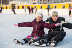 O irmão e a irmã caíram ao patinar e ao ter o divertimento Imagens de Stock