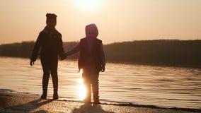 O irmão e a irmã estão tendo o divertimento pelo rio no por do sol video estoque