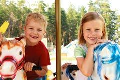 O irmão e a irmã montam o carrossel Fotografia de Stock