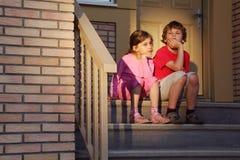 O irmão e a irmã sentam-se em escadas Fotografia de Stock