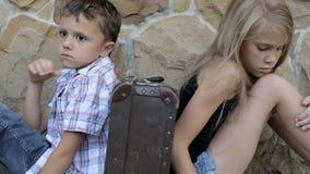 O irmão e a irmã tristes estão sentando-se pela parede com uma mala de viagem no tempo do dia video estoque