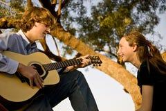 O irmão joga a guitarra para a irmã pequena. Fotos de Stock