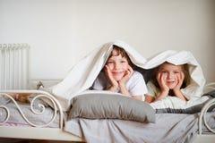 O irmão mais novo e a irmã fizeram um jogo na cama no quarto fotos de stock