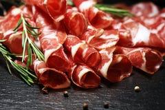 O italiano cortou o coppa curado com especiarias Presunto cru Crudo ou jamon com alecrins imagens de stock royalty free