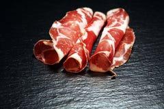O italiano cortou o coppa curado com especiarias Presunto cru Crudo ou jamon com alecrins imagens de stock