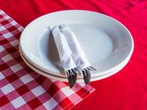 O jantar, os pratos e a cutelaria de espera limparam em toalhas vermelhas fotos de stock royalty free