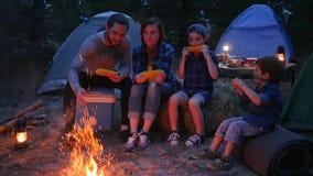O jantar perto das chamas na natureza, família da família come o milho com sal, curso acampando, mamãe, paizinho e os filhos come