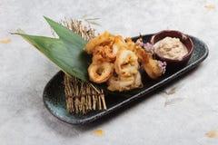 O japonês fritou o calamar de mistura Karaage da farinha do tempura do calamar servido com molho no papel japonês do washi da pla Imagens de Stock Royalty Free