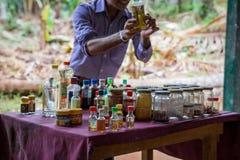 O jardim da especiaria O homem mostra especiarias e óleos de Ayurvedic Imagem de Stock