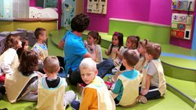 O jardim de infância, professor joga com grupo de crianças, acampamento do fim de semana, experiência e jogo, os métodos os mais  video estoque